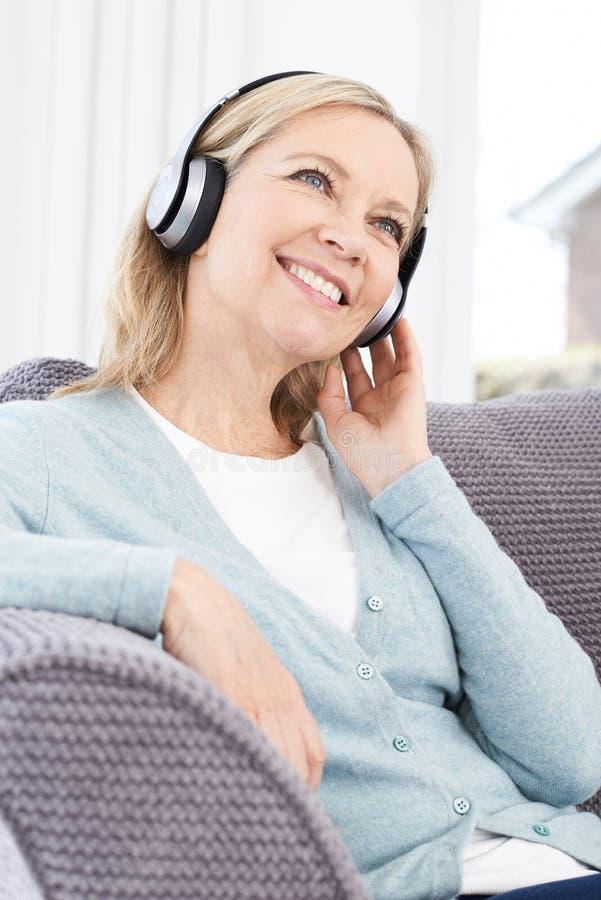 Mulher madura que escuta a música em fones de ouvido sem fio foto de stock royalty free