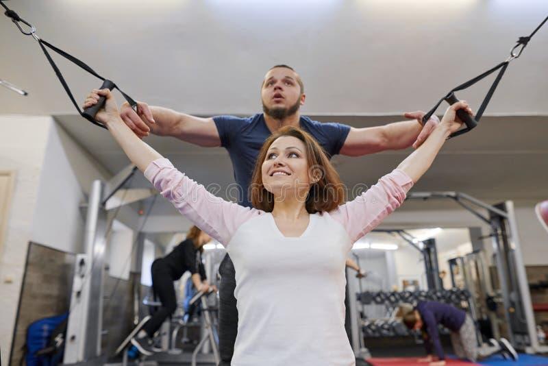 Mulher madura que faz o exercício em simuladores da descompressão com reabilitação do instrutor Fisioterapeuta dos esportes que a foto de stock