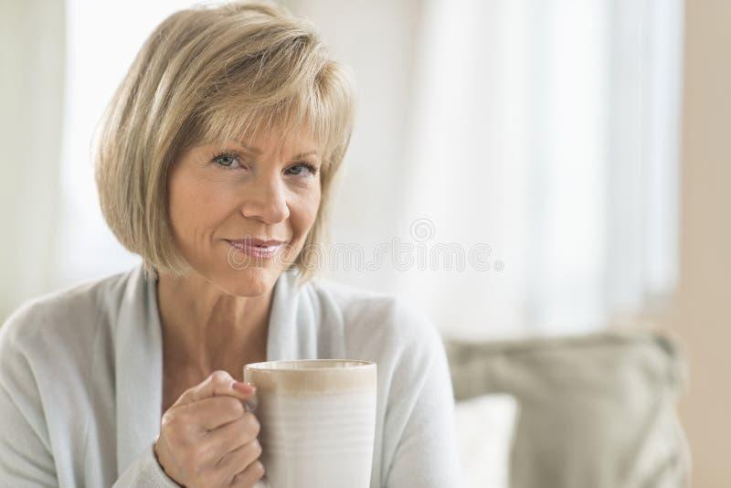 Mulher madura que guarda a caneca de café em casa imagem de stock royalty free