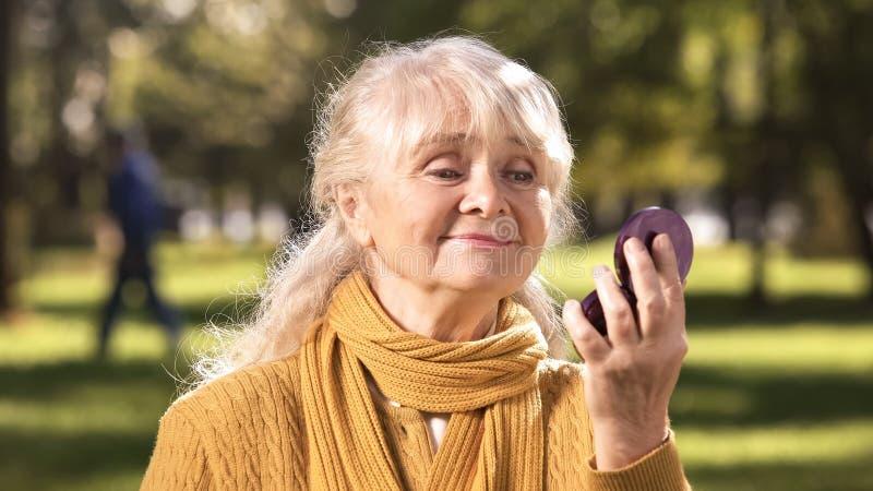 Mulher madura que olha sua reflexão no espelho compacto que senta-se no parque foto de stock
