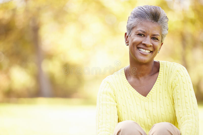 Mulher madura que relaxa em Autumn Landscape foto de stock royalty free