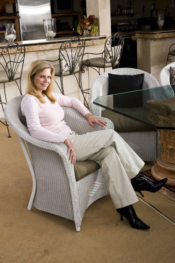 Mulher madura que relaxa na cadeira de vime imagem de stock