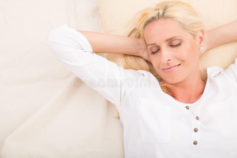 Mulher madura que relaxa na cama imagens de stock royalty free
