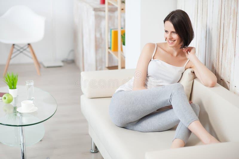Mulher madura que relaxa no sofá fotos de stock royalty free