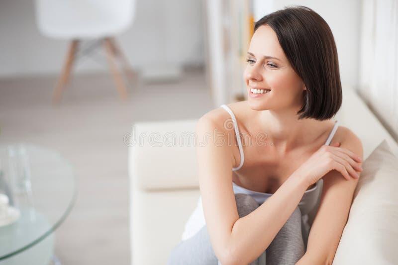 Mulher madura que relaxa no sofá imagem de stock royalty free