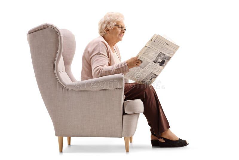 Mulher madura que senta-se em uma poltrona e que lê um jornal imagens de stock