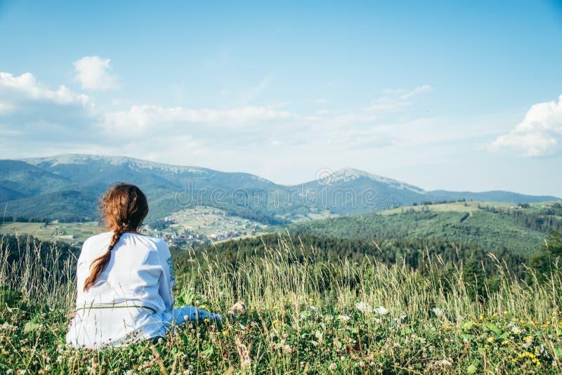 Mulher madura que senta-se no pico do monte e que enjoing a vista foto de stock