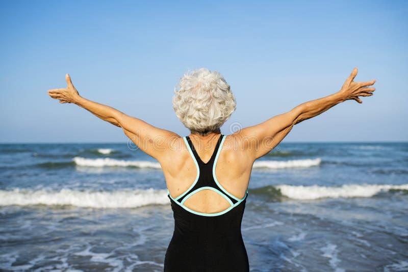 Mulher madura que sente livre na praia imagem de stock