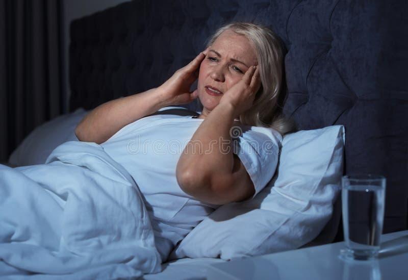 Mulher madura que sofre da dor de cabeça na cama foto de stock royalty free