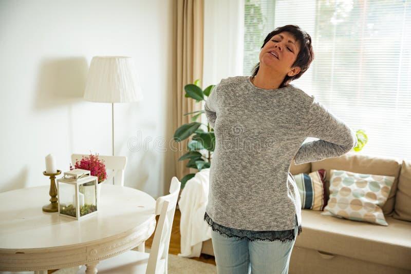 Mulher madura que sofre da dor lombar imagem de stock royalty free