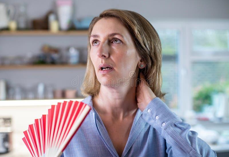 Mulher Madura Que Sofre Hot Flush Da Menopausa Usando Ventilador imagens de stock