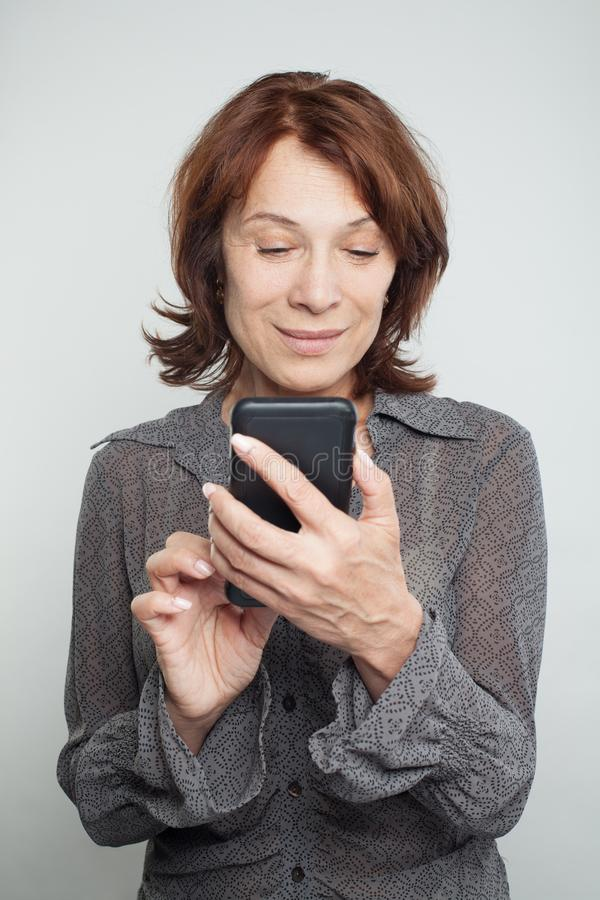 Mulher madura que texting no fundo branco fotos de stock royalty free