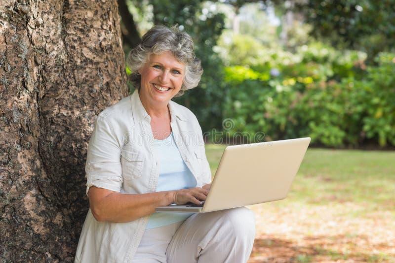 Mulher madura que usa um portátil que senta-se no tronco de árvore fotos de stock