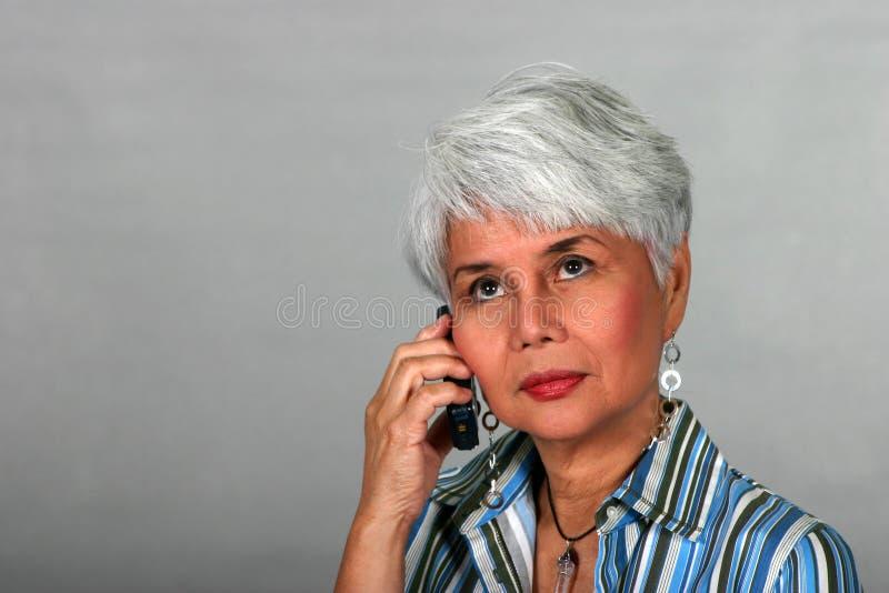 Mulher madura que usa um telefone de pilha fotos de stock royalty free