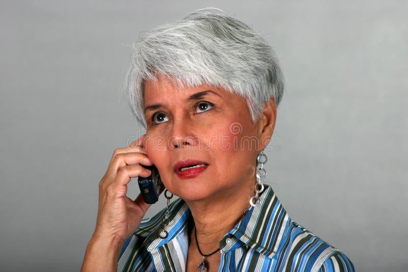 Mulher madura que usa um telefone de pilha imagens de stock royalty free