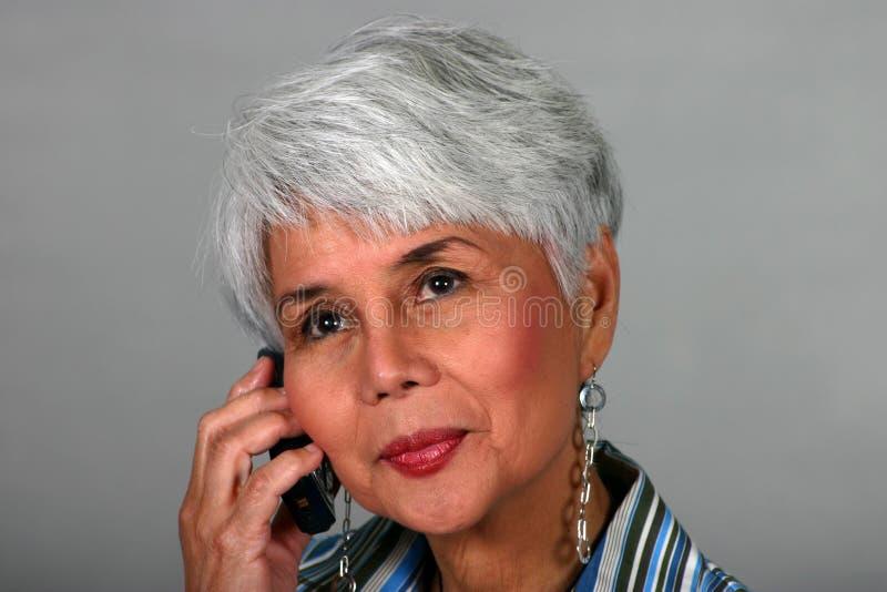 Mulher madura que usa um telefone de pilha imagem de stock