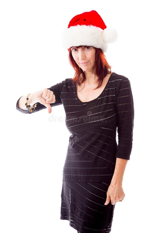 A mulher madura que veste o chapéu de Santa e que mostra manuseia abaixo do sinal fotos de stock royalty free