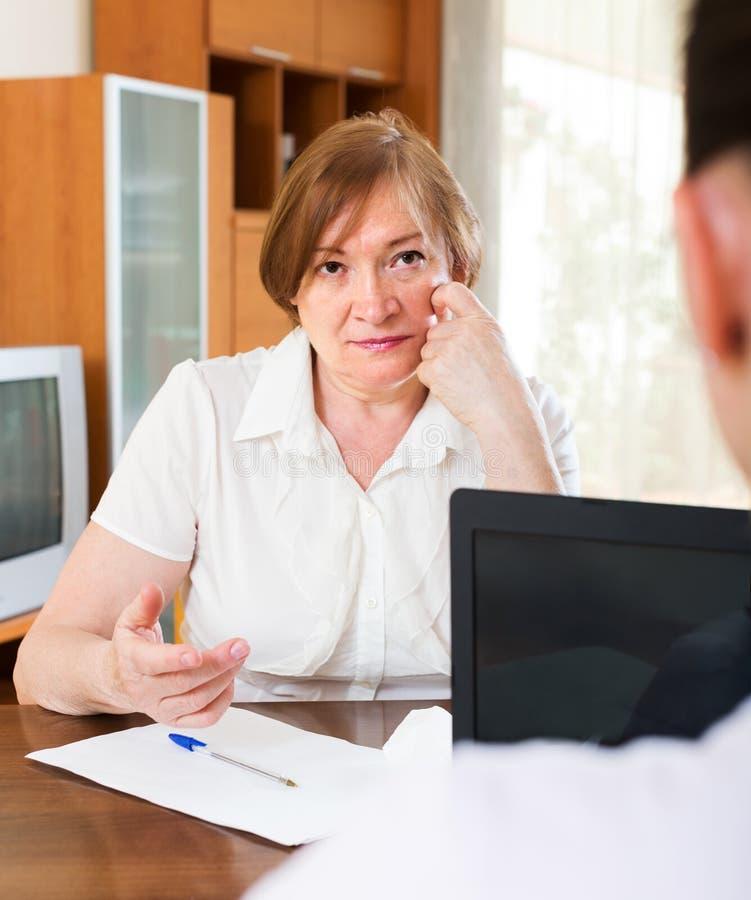 A mulher madura responde a perguntas do trabalhador foto de stock