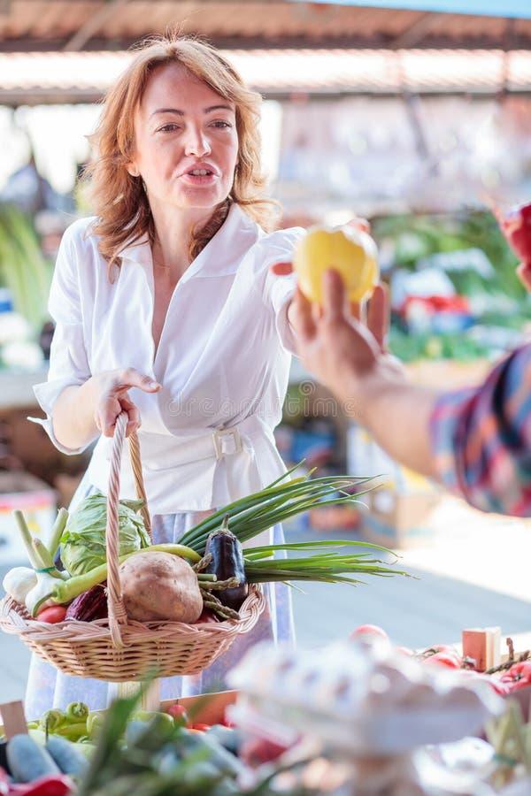Mulher madura séria que compra vegetais orgânicos frescos em um mercado local foto de stock