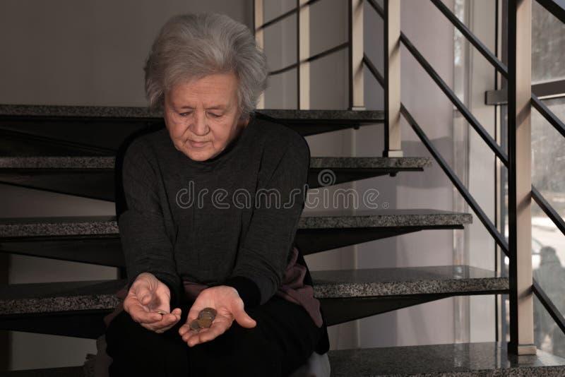 Mulher madura virada pobre com as moedas em escadas fotos de stock royalty free