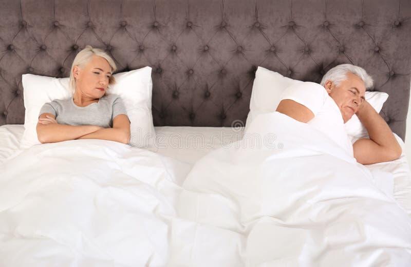 Mulher madura virada que encontra-se na cama perto de seu marido de sono em casa fotos de stock