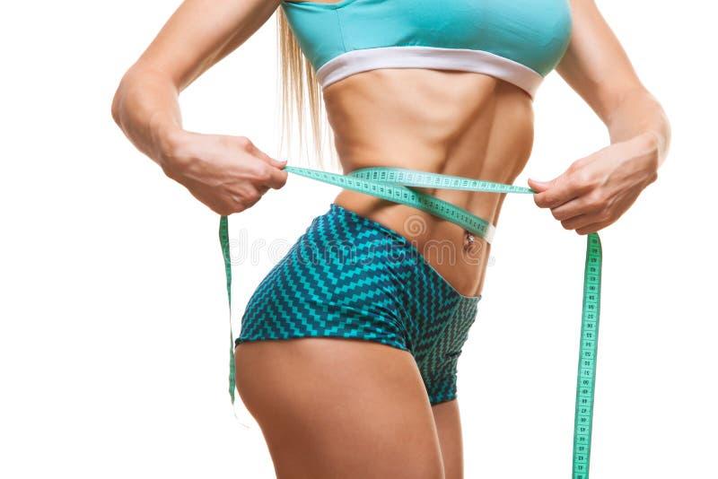 Mulher magro atlética que mede sua cintura pela medida da fita após uma dieta sobre o fundo preto imagens de stock