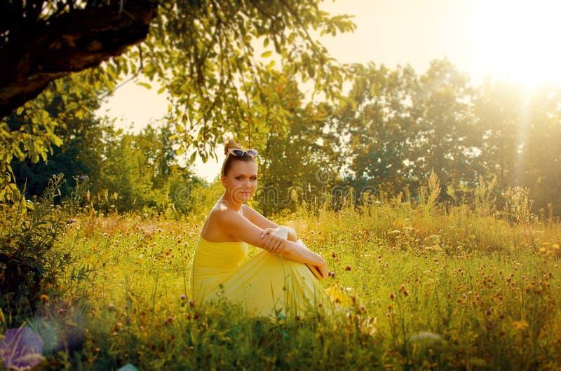 Mulher magro bonita no vestido amarelo que senta-se na grama no foto de stock royalty free