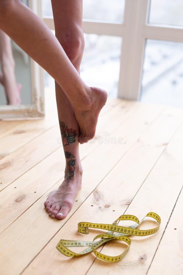Mulher magro com os pés longos que estão em um pé perto da janela imagem de stock