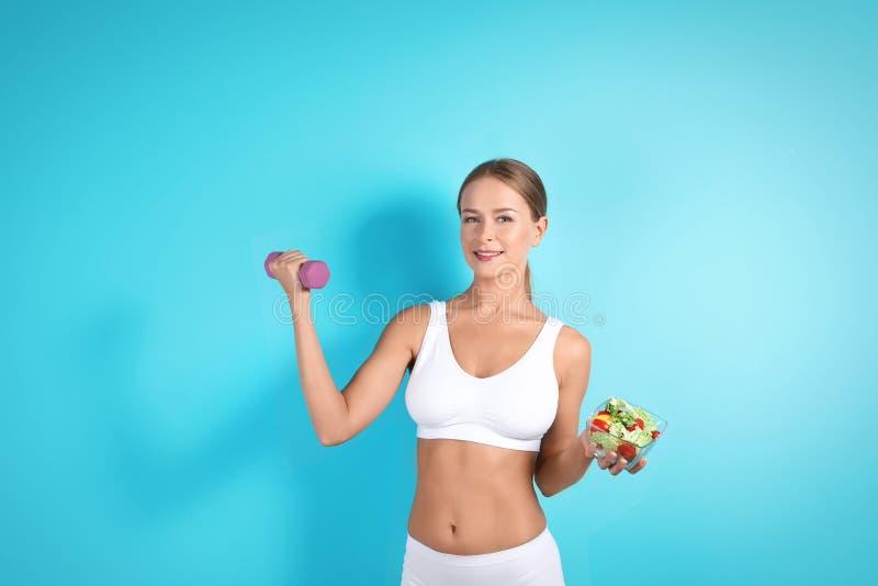 Mulher magro com salada e peso foto de stock royalty free