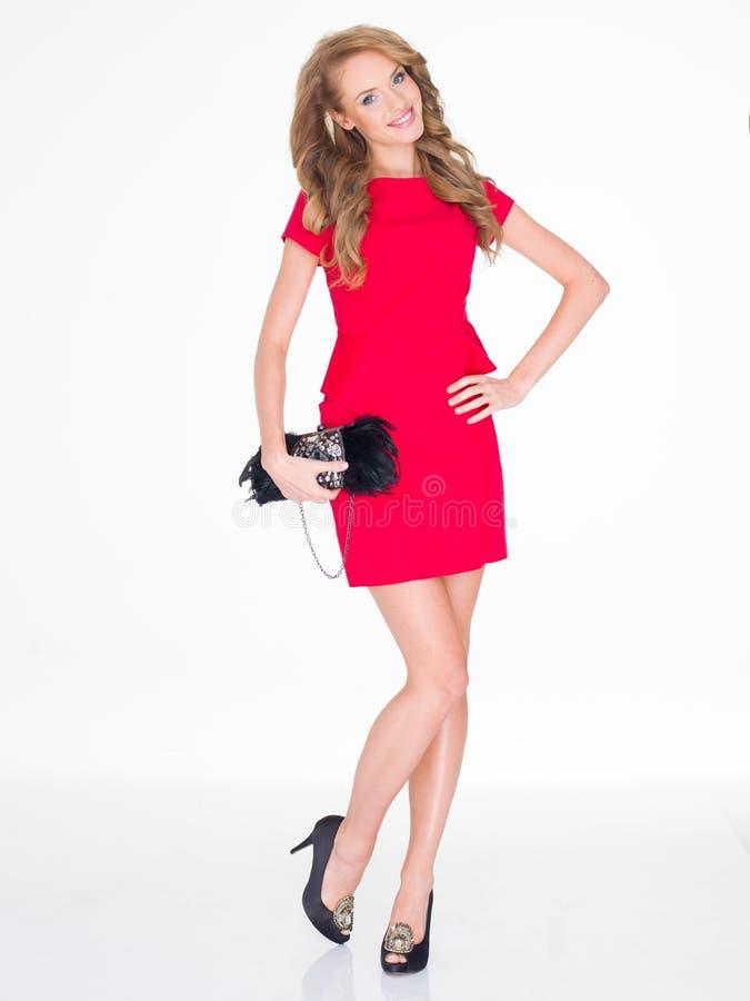 Mulher magro de sorriso no vestido vermelho que guarda a bolsa fotografia de stock royalty free