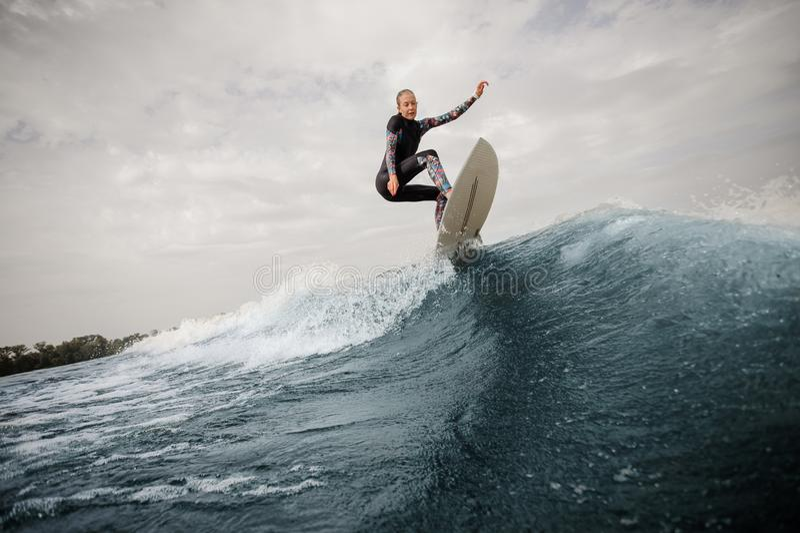 Mulher magro e ativa nova no roupa de banho que salta acima do aga azul da onda imagem de stock