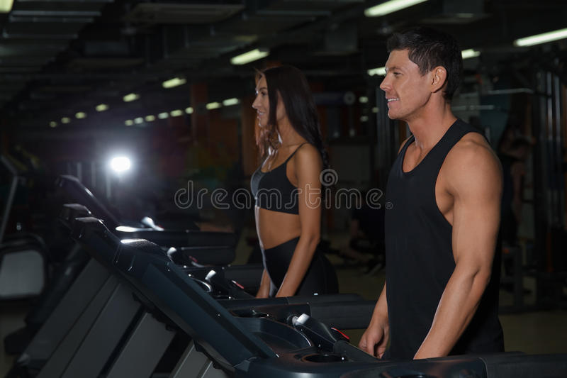 Mulher magro e instrutor masculino muscular no gym do esporte imagem de stock royalty free