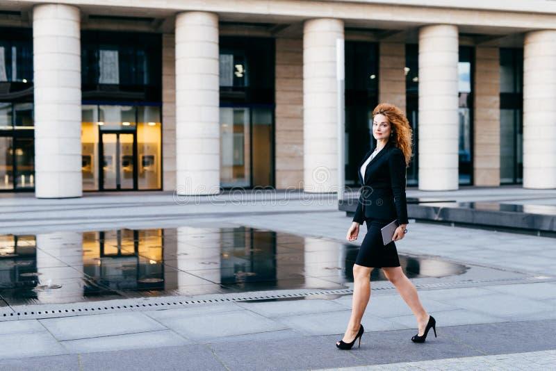 Mulher magro elegante no terno preto e nas sapatas alto-colocadas saltos, guardando a tabuleta nas mãos que vão para o trabalho M imagem de stock