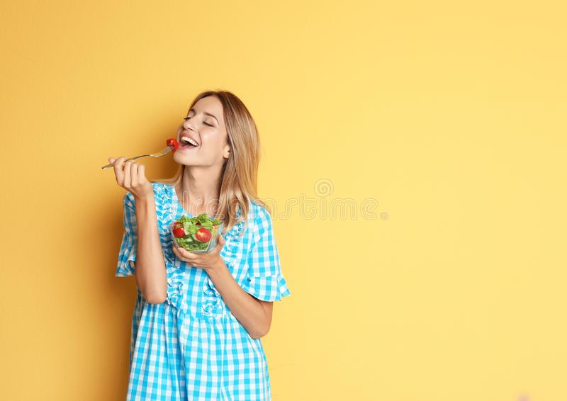 Mulher magro feliz com salada no fundo da cor fotos de stock