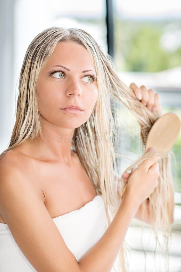 Mulher magro loura na toalha que penteia o cabelo longo molhado fotografia de stock