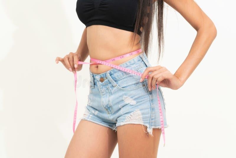 A mulher magro mede sua cintura com fita de medi??o foto de stock