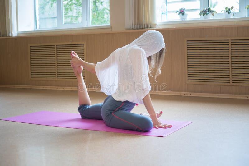 Mulher magro nova com o cabelo louro que senta-se na esteira da ioga e que faz esticando exercícios - puxa o pé para o corpo fotos de stock royalty free