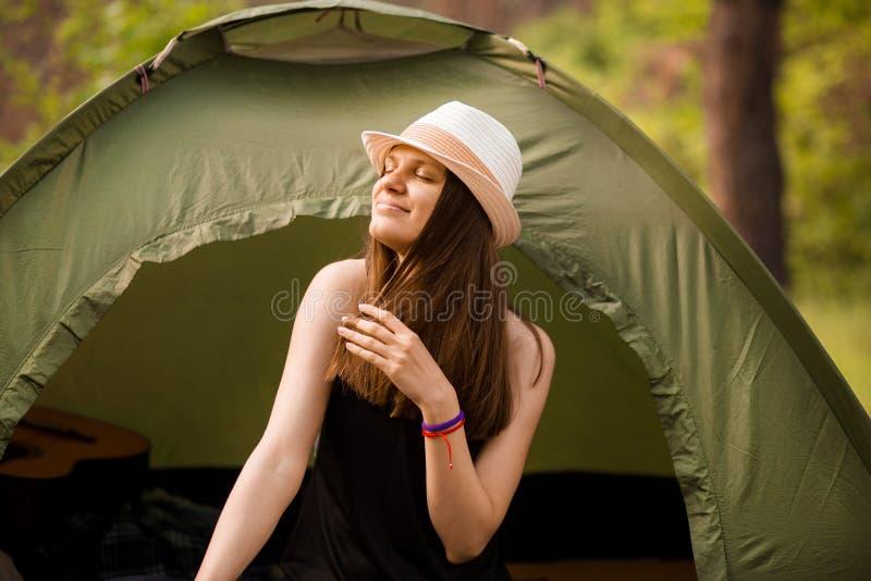 Mulher magro nova do caminhante que senta-se na barraca pequena do turista que aprecia a floresta bonita da natureza na manh? bri fotos de stock