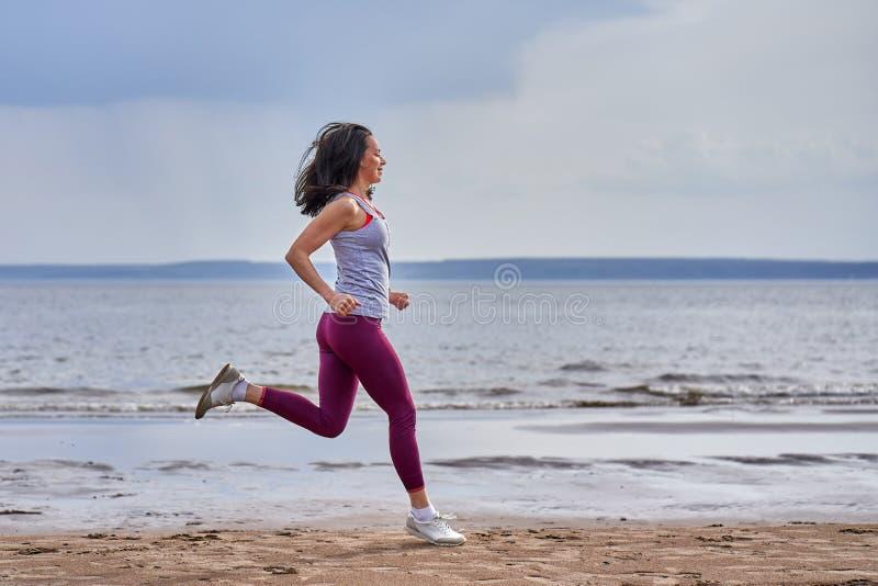 Mulher magro nova em corridas do sportswear ao longo do banco arenoso de um grande rio imagens de stock