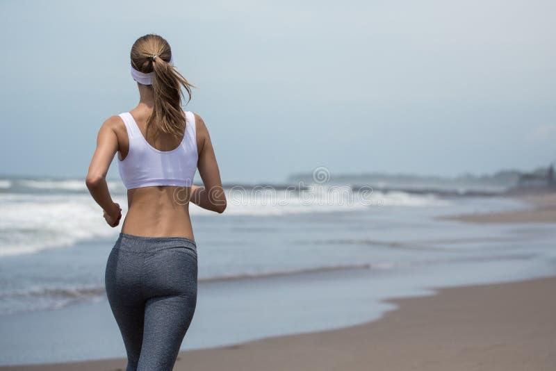 Mulher magro nova que corre na praia Vista traseira imagens de stock