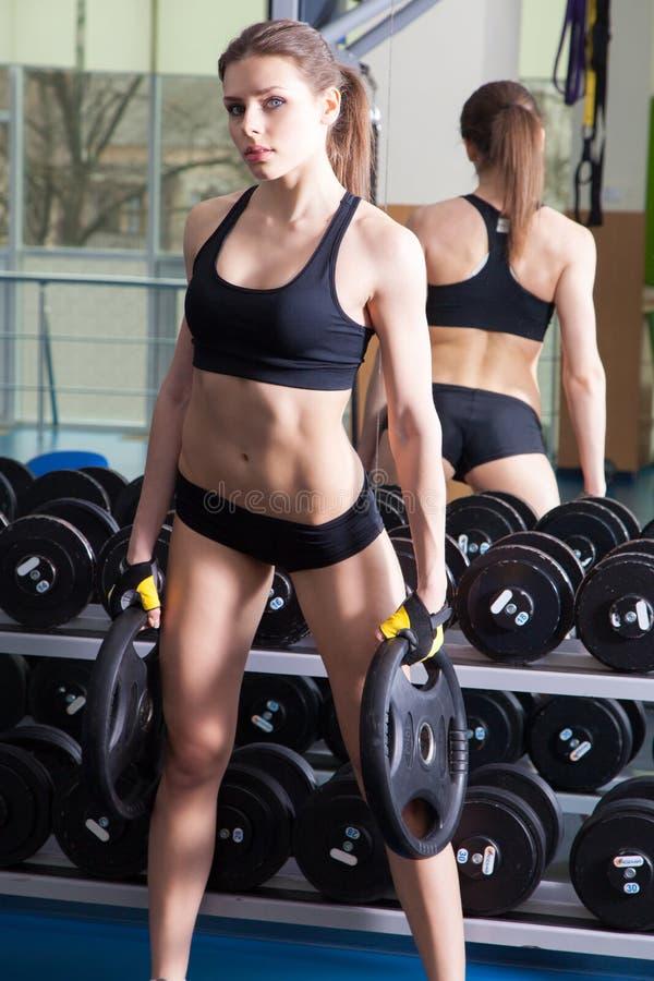Mulher magro nova que exercita em um gym imagens de stock