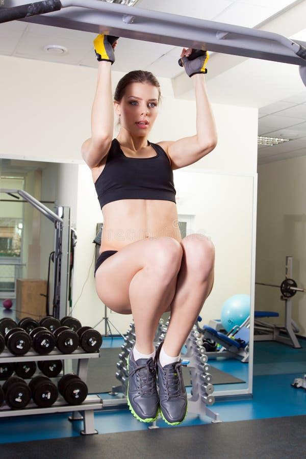 Mulher magro nova que exercita em um gym imagem de stock royalty free