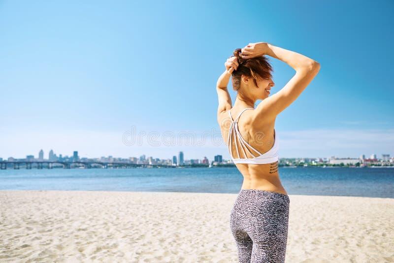 Mulher magro 'sexy' bonita na praia da cidade da areia com fundo do mar Conceito do ver?o Vista traseira fotografia de stock