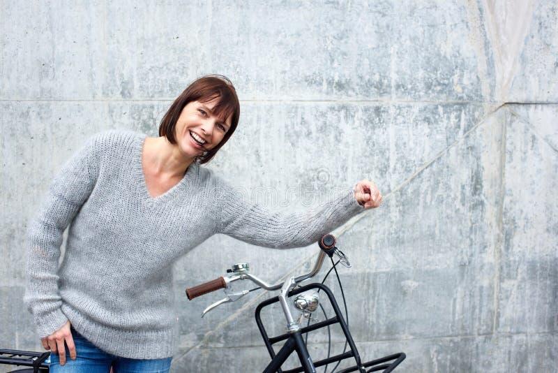 Mulher mais idosa alegre com bicicleta fotografia de stock royalty free