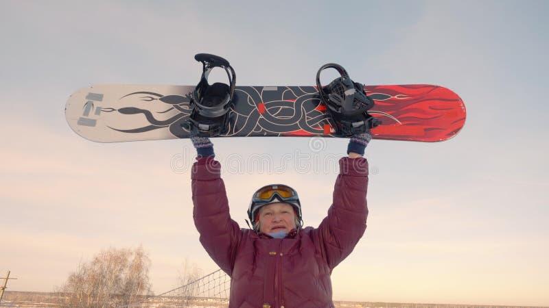 Mulher mais idosa alegre que aumenta o snowboard na inclinação nevado no recurso do inverno imagem de stock