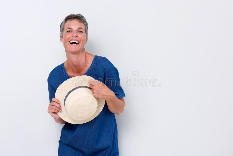 Mulher mais idosa alegre que ri com o chapéu contra o backgorund branco foto de stock royalty free
