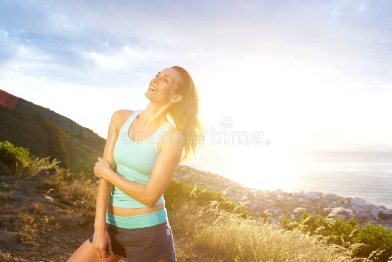 Mulher mais idosa apta que sorri fora no por do sol imagem de stock royalty free