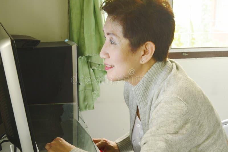 A mulher mais idosa asiática aprecia trabalhar com computador pessoal fotos de stock royalty free