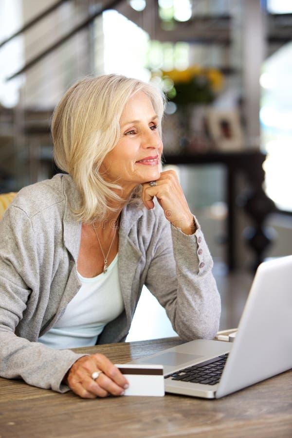 Mulher mais idosa atrativa com laptop e cartão de crédito imagem de stock