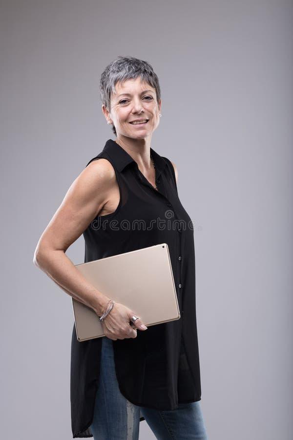Mulher mais idosa atrativa na moda que guarda um tabuleta-PC imagens de stock royalty free